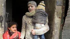 Des enfants sortent d'un édifice après un bombardement sur la ville d'Alep, en Syrie, le 3 janvier.