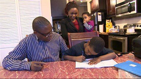 Philbert Ngenzirabona aide son fils Ryan à faire ses devoirs, sous le regard de sa femme Consolate Nzeyimana et de leur fille, le 23 janvier 2014 à Regina dans l'ouest du Canada..