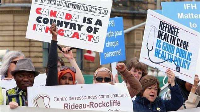 Des manifestants contre la réforme des soins de santé aux réfugiés, devant la colline du Parlement, à Ottawa.