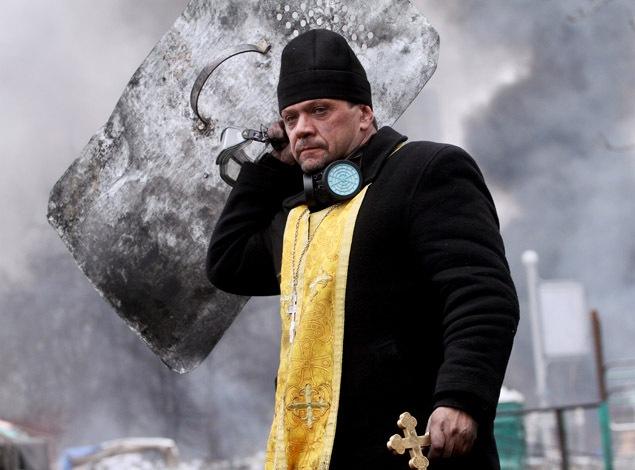 Un prêtre orthodoxe tient une croix et un bouclier lors d'un affrontement avec les policiers anti-émeute dans le centre de Kiev.