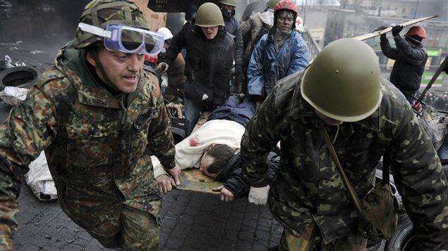 Des manifestants portent une personne blessée lors d'affrontements avec la police, près de la place de l'Indépendance, à Kiev, le 20 février 2014.