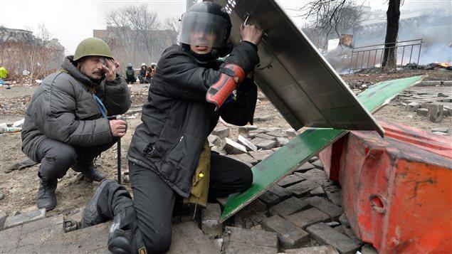 Des manifestants se protègent lors d'affrontements avec les policiers.