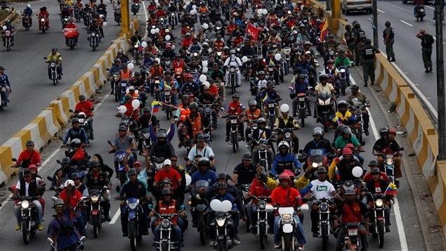 Des partisans du président Maduro défilent à Caracas à motos pour rejoindre l'autoroute bloquée par les manifestants opposés au gouvernement.