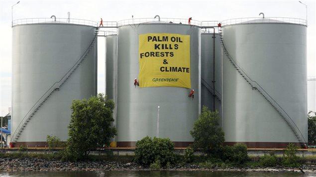 En Indonésie, en 2007, une bannière est déployée par Greenpeace sur des réservoirs d'huile de palme.