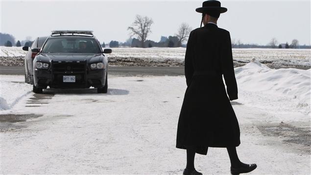 Un membre de la secte Lev Tahor déambule dans la rue devant un véhicule d'urgence pendant le déroulement des procédures à Chatham, en Ontario, le 5 mars.