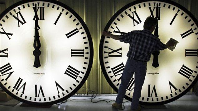 Un ouvrier nettoie des horloges