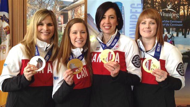 Les curleuses manitobaines Jennifer Jones (gauche), Kaitlyn Lawes, Jill Officer et Dawn McEwen (droite) montrent, le 13 mars 2014 à l'hôtel de ville de Winnipeg, les médailles d'or qu'elles ont remporté aux Olympiques d'hiver de Sotchi.