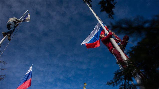 Des militants pro-russes décrochent les drapeaux ukrainiens du quartier général de la marine ukrainienne à Sébastopol pour les remplacer par des drapeaux russes.