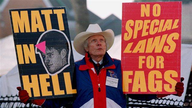 En 1999, Fred Phelps brandit des pancartes aux discours homophobes lors du procès d'un des des meurtriers de Matthew Shepard, un jeune universitaire homosexuel.