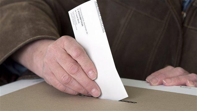 Un électeur dépose son bulletin dans une boite de scrutin.
