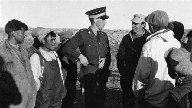 Un officier de la Gendarmerie royale du Canada s'entretient avec un groupe d'Inuits des îles Belcher, en 1949.