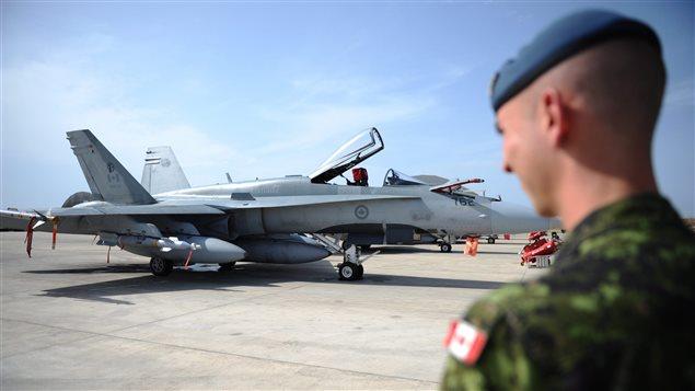 Un soldat regarde un CF-18. En 1991, le Canada a engagé 26 CF-18 dans la guerre du Golfe dans l'Operation FRICTION.