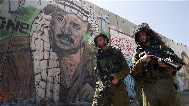 Des soldats israéliens devant le mur construit par Israël autour de la Cisjordanie.