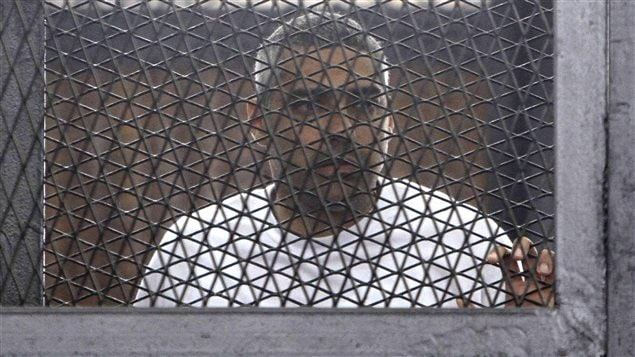 Le journaliste Mohamed Fahmy dans une cage au palais de justice de l'Académie de police au Caire