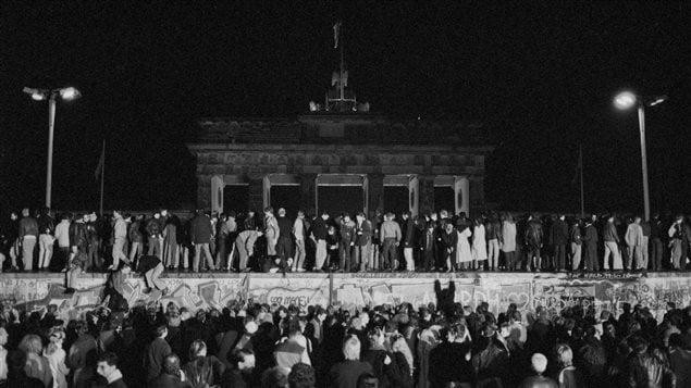 Des Allemands de l'Est et de l'Ouest célèbrent la chute du mur de Berlin et l'ouverture de frontière est-allemande à la porte de Brandebourg, le 9 novembre 1989.