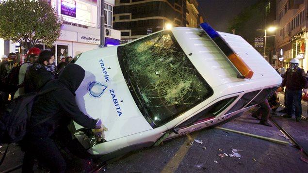 Des manifestants renversent une camionnette de police lors d'une émeute jeudi soir, à Kadikoy.