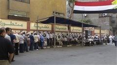 Des électeurs égyptiens attendent en file indienne devant un bureau de vote du Caire, lundi, pour élire leur nouveau Président