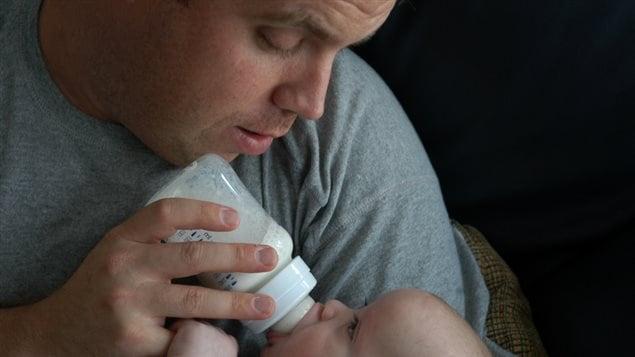 Un homme nourrit un bébé au biberon