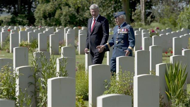 Le premier ministre canadien Stephen Harper s'entretient avec le major général, Richard Rohmer, dans le cimetière canadien de Bény sur mer dans le cadre du 70e anniversaire du débarquement de Normandie.