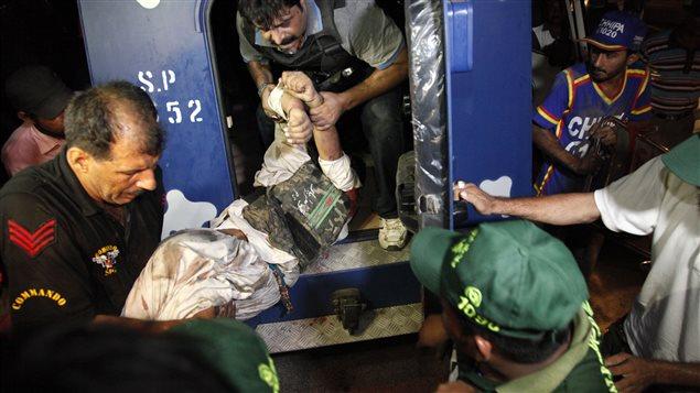 Des policiers aident un collègue blessé dans l'attaque de l'aéroport de Karachi, le 8 juin.