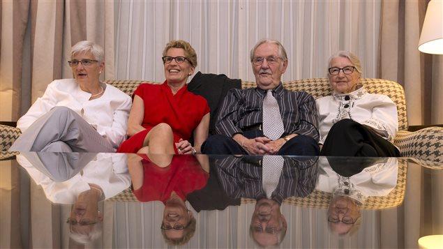 La première ministre réélue Kathleen Wynne (en rouge) regarde défiler à la télévision les résultats des élections en compagnie de ses parents et de sa conjointe Jane Rounthwaite.