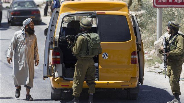 Des soldats isréaliens fouillent un véhicule palestinien près de la ville d'Hébron, en Cisjordanie.