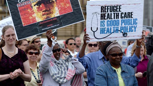 Des manifestants devant le parlement à Ottawa manifestait en juin 2014 contre les réductions dans les soins de santé aux réfugiés.