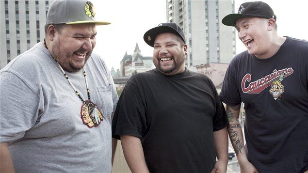 Les membres du groupe A Tribe Called Red. À droite, Ian DJ NDN porte le fameux chandail au logo jugé raciste par certains. À gauche, Bear Witness, et au centre, DJ Shub.