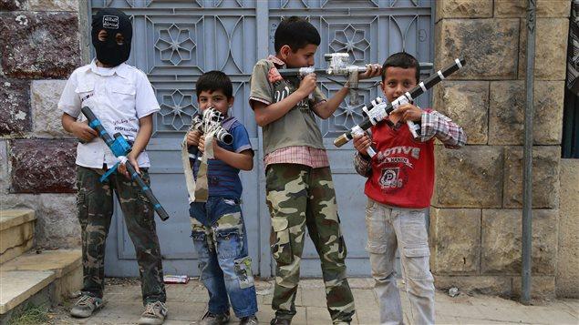Niños posan armados con fusiles falsos el 8 de junio en Alepo.