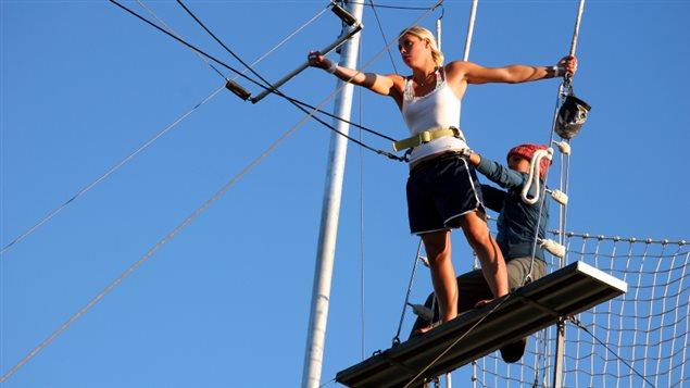 Un femme effectue un saut en trapèze
