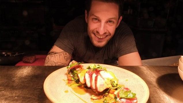 Guillaume St-Pierre du Restaurant La Planque, derrière son assiette de porc