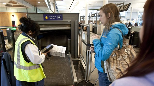 A female border security officer on the left with a yellow vest over her uniform checks the papers of a young woman in a blue jacket with a large bag over her shoulders in front of mechanical security device that monitors the contents of bags.