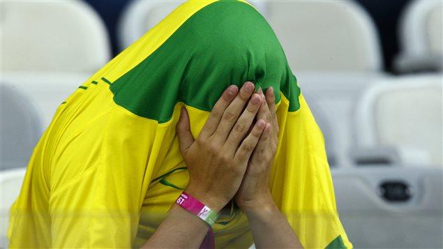 Un partisan brésilien cache sa peine en s'enfouissant la tête dans les couleurs nationales.
