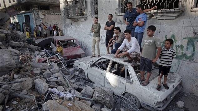 Des enfants se tiennent près d'une maison détruite à Rafah.