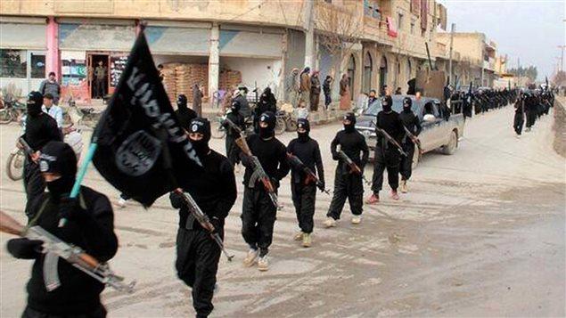 Des militants de l'organisation armée djihadiste l'État islamique marchent à Raqqa, en Syrie.