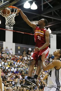 Canadian Andrew Wiggins of Cleveland dunks against Milwaukee in an NBA summer league basketball earlier this month. Wiggins was the NBA's top draft choice this spring. He wearing a red unform and is well over the basket, dunking the ball with his right hand. The ball has just passed the top of the rim. A helpless Milwaukee player in white is to Wiggins's left but well below him. A crowd of spectators about 20 rows high watches in the background.