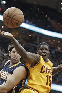 Canadian Anthony Bennett, right, grabs a rebound ahead of Indiana's Luis Scola, of Argentina, during an NBA basketball game between Cleveland and Indiana in January. Bennett was the NBA's top draft choice in 2013. Bennett is wearing a mainly yellow jersey with red trim and the number 15 on his uniform. He is tapping the basketball with his right hand stretched to his right at about head level.  Scola in dark blue is to Bennett's left and boxed out by Bennett's big body.