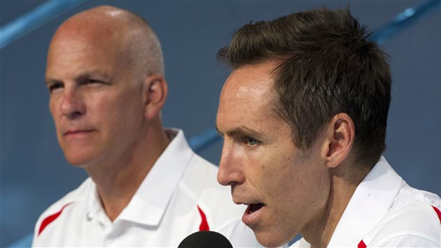 Can Basketball Canada general manager Steve Nash, right, and head coach Jay Triano lead the Canadian national team to greater glory by qualifying for the 2016 Rio Olympics? Nash has short black hair and is speaking into a microphone with great intensity. Triano sits quietly to his left, listening. He is a bald man, older than Nash, who is 40. Each is wearing a Team Canada white polo shirt.