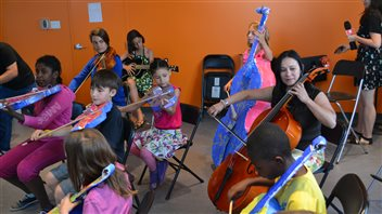 Orchestre de papier et vrai violoncelle en répétition