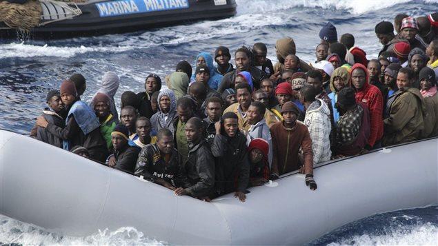 Des migrants dans un bateau de sauvetage italien après une opération de sauvetage au large de la Sicile, en 2013