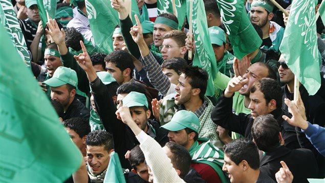 Des étudiants palestiniens tiennent des drapeaux du Hamas.