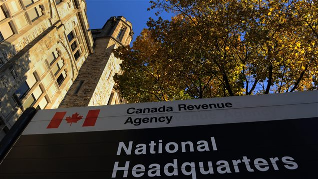 "The Canada Revenue Agency headquarters in Ottawa. It is directing audits on at least 52 Canadian charities. The photo shows a beautiful fall day with leaves still on a giant maple that rises at the right of picture. On the left is the headquarters, a Victorian grey and tan brick building with a tower reaching up to a crisp azure sky. At the bottom of the picture in the foreground is a sign identifying the building. We ""Canada Revenue Agency"" printed at the top of the sign in black letters on a white base. To the left of that part of the sign is a logo of the Canadian flag in white and red. On the main body of the sign National Headquarters written in white on a black background."