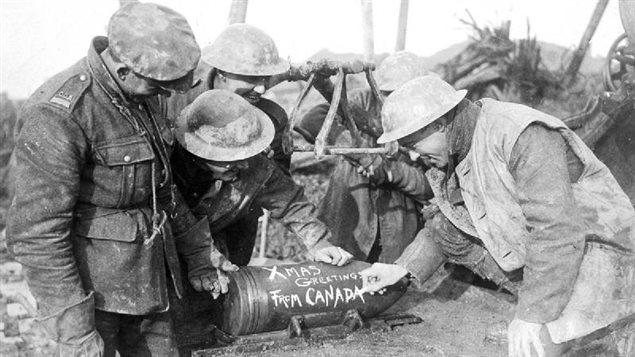 Des soldats de l'artillerie canadienne ajoutent un message à leur projectile