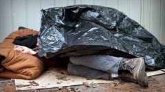 At least 30,000 Canadians are homeless on any given night. We see a man sleeping under a black plastic garbage bag. His feet stick out from underneath while his head rests of what appears to be a sleeping bag.