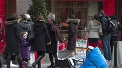 Estimates say 150,000 to 300,000 Canadians experience homelessness in any given year. The photo shows a person huddled under a blue blanked as holiday shoppers walk by in downtown Toronto. A Christmas tree with lights lit is in the background.