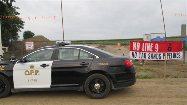 """Protesters set up a blockade at an Enbridge pipeline site in southwestern Ontario on Tuesday, disrupting work on what is called Line 9. The photo shows a mainly black OPP police car in the left foreground sitting on a dirt road. Behind the car to the right is a red and white sign that says at the top in capital letters over the red """"NO LINE NINE."""" Below that, on the white base, is written (again in capital letters) """"NO TAR SANDS PIPELINES."""" The background is composed brown, flat land."""