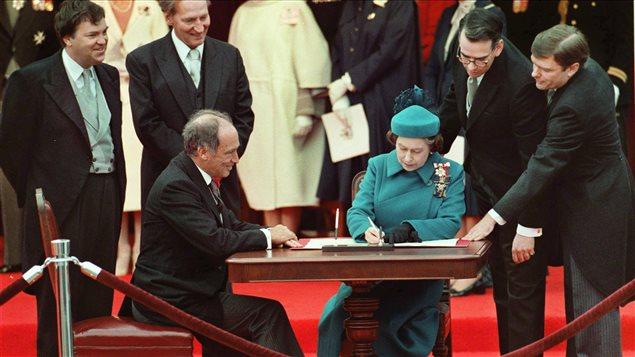 Signature de la Constitution canadienne par la reine Élisabeth II à Ottawa le 17 avril 1982, en présence du premier ministre Pierre Elliott Trudeau.