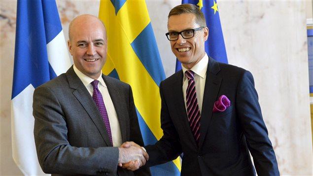 Le premier ministre suédois Fredrik Reinfeldt (à gauche) serre la main du premier ministre finlandais Alexander Stubb.
