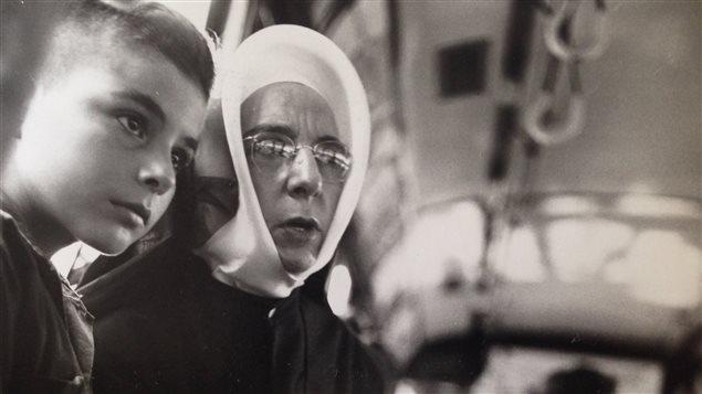 Lida Moser : Une religieuse accompagnant un jeune garçon dans un autobus, à Montréal, été 1950, gélatine argentique, 17,6 x 18 cm (P728,DM3,P96)