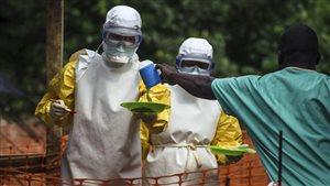 Du personnel de Médecins sans frontières apporte de la nourriture à des patients placés en isolation en raison du virus de l'Ebola, en Sierra Leone.